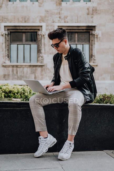 Giovane uomo serio intelligente seduto su una recinzione di marmo con notebook sulle ginocchia e digitando — Foto stock