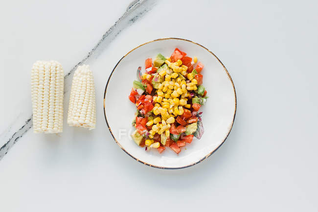 Tigela servida com milho, tomates cortados e abobrinha na mesa — Fotografia de Stock