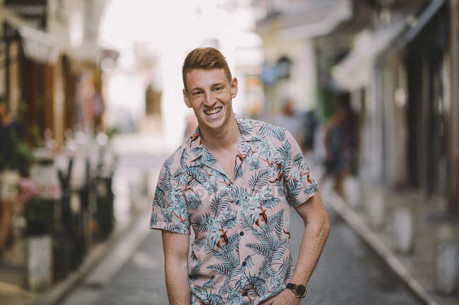 Красивый счастливый мужчина в гавайской рубашке стоит на улице, смотрит в камеру и улыбается. — стоковое фото