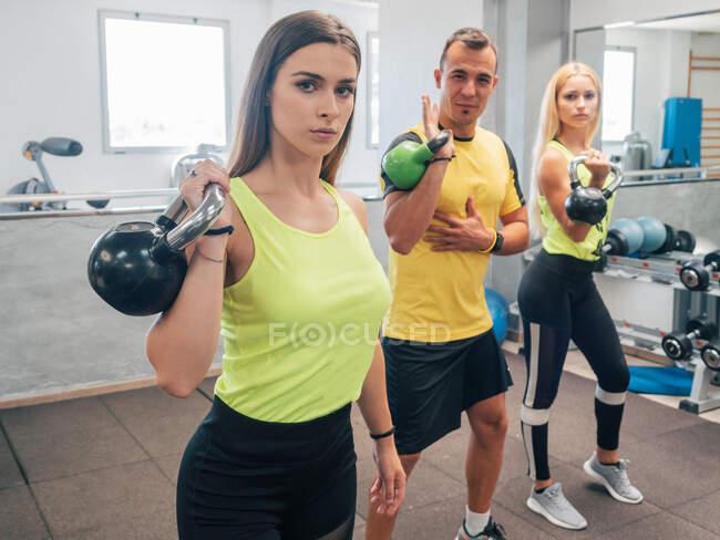 Сильные мужчины и женщины поднимают гири во время тренировки в тренажерном зале — стоковое фото