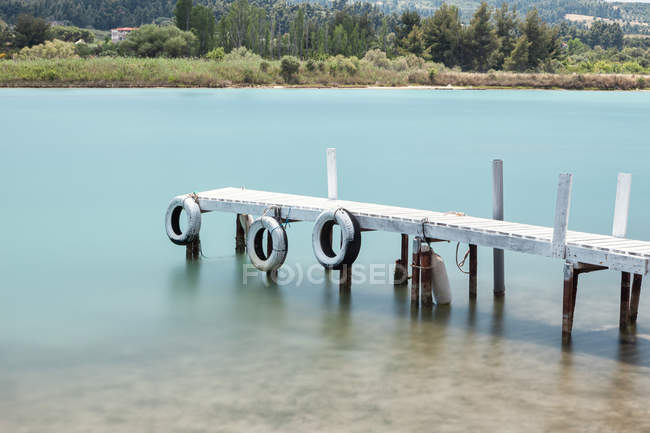 Abandoned destroyed pier in crystal blue water, Halkidiki, Greece — Stockfoto