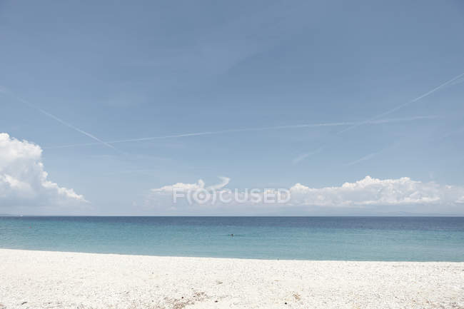 Picturesque calm seashore with clouds on horizon and white sandy beach in sunny day, Halkidiki, Greece — стокове фото