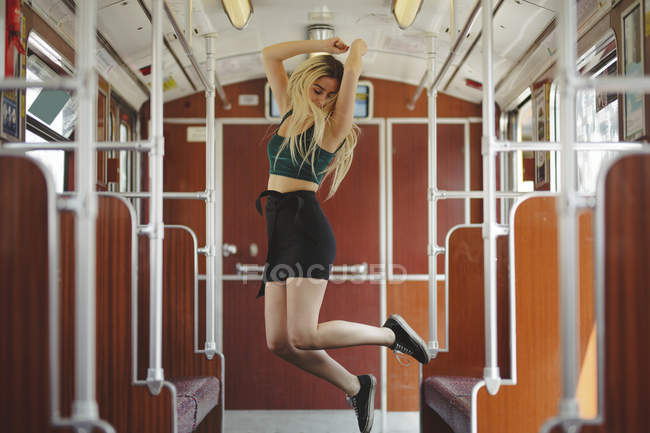 Young blonde woman jumping in train car in Berlin — Stock Photo