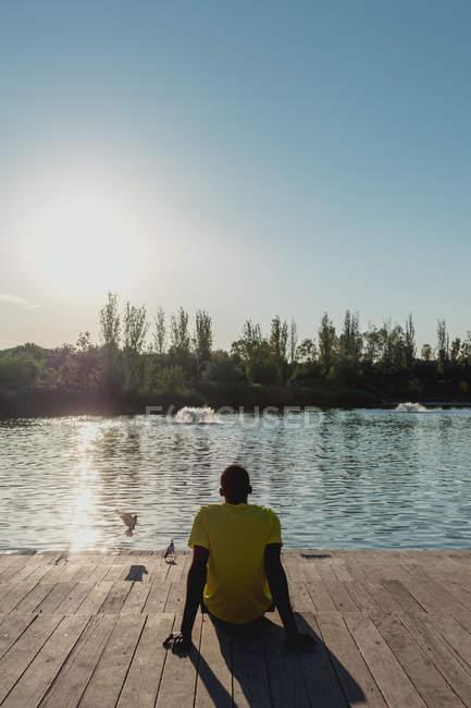 Visão traseira do homem sentado no cais de madeira apoiado nas mãos para descansar durante o dia ensolarado — Fotografia de Stock