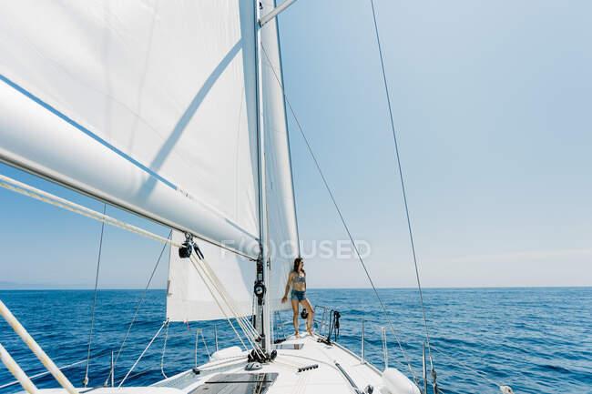 Вид сбоку путешествующей женщины в купальнике, стоящей на боку яхты в море и отводящей взгляд — стоковое фото
