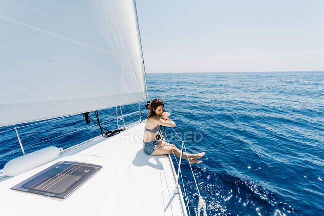 Vista laterale della donna che viaggia indossando costume da bagno seduto sul lato dello yacht in mare guardando altrove — Foto stock