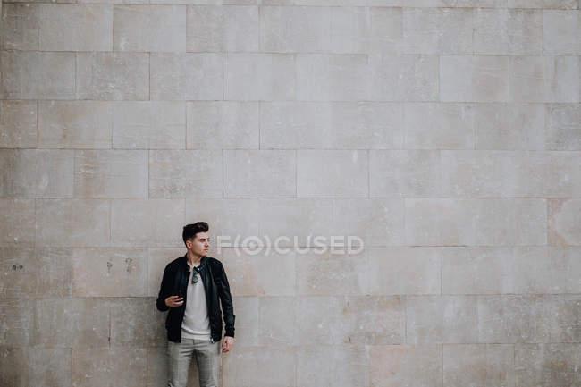 Smart stylish man holding mobile phone against plain brick wall — Stock Photo