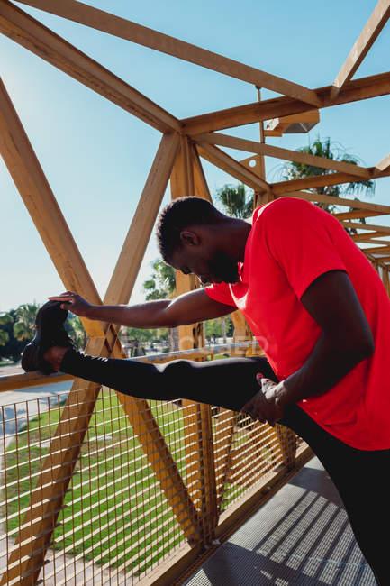 Homme noir sportif pliant le genou et s'échauffant sur un pont de fer pendant la journée ensoleillée — Photo de stock
