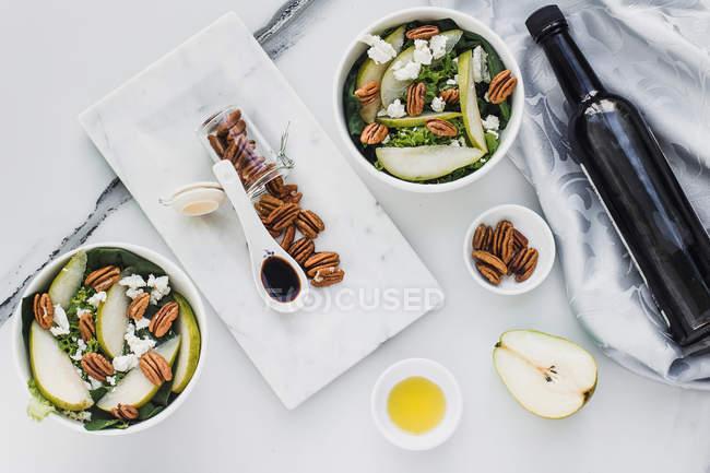 Servierte Schalen mit geschnittenen Birnen und Pekannüssen auf dem Tisch mit einer Flasche Sojasauce — Stockfoto