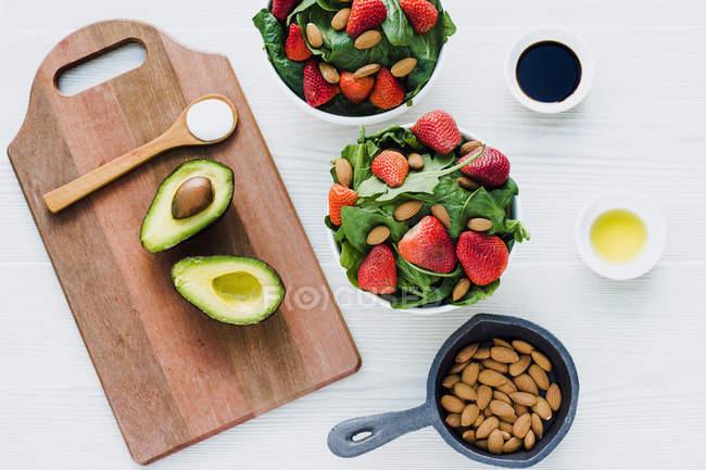 Tigelas com morangos, amêndoas e verdura na mesa com abacate e colher de molho na tábua de corte — Fotografia de Stock