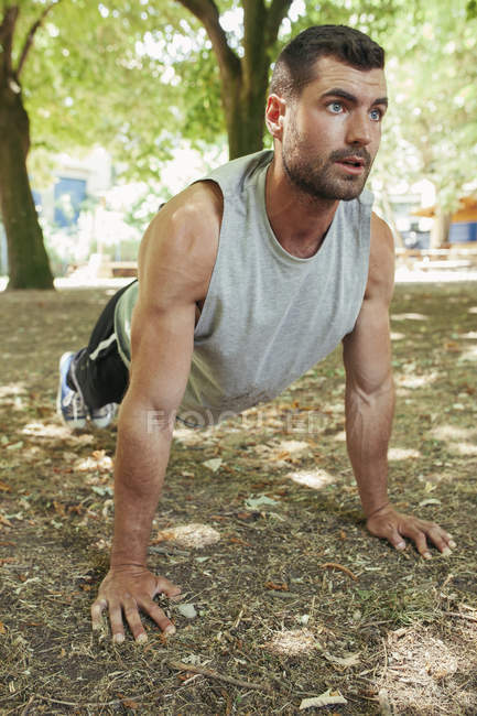 Handsome focused muscular man in sportswear doing push up exercise in park on sunny day — Stock Photo