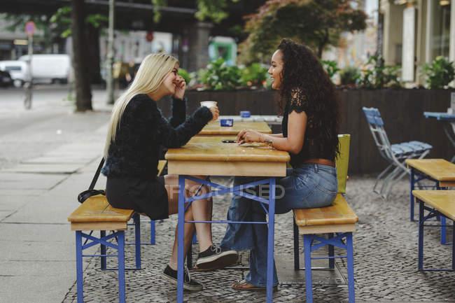 Вид сбоку красивых молодых женщин, сидящих в берлинском уличном кафе, говорящих и смеющихся — стоковое фото