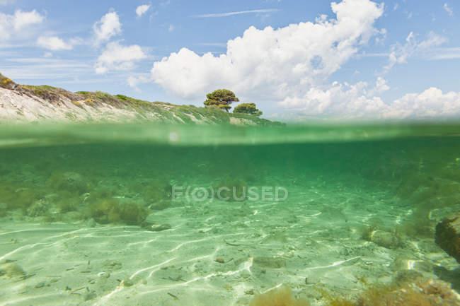 Vista pittoresca dell'isola rocciosa e del fondo del mare nella soleggiata giornata estiva a Halkidiki, Grecia — Foto stock