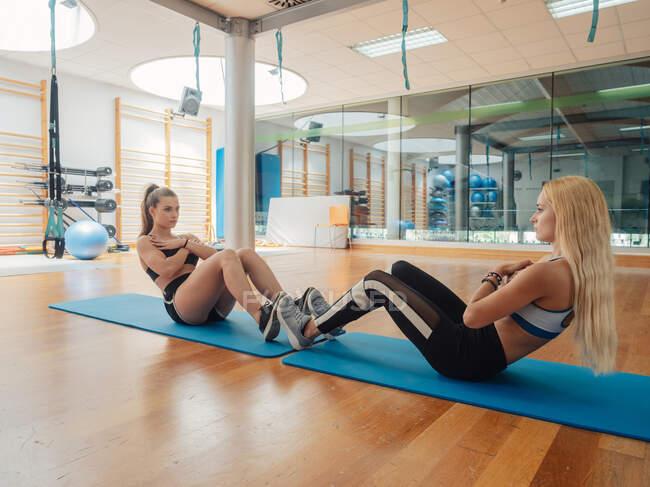 Dos mujeres musculosas delgadas en ropa deportiva haciendo ejercicio abdominal mirándose en la estera en el gimnasio - foto de stock