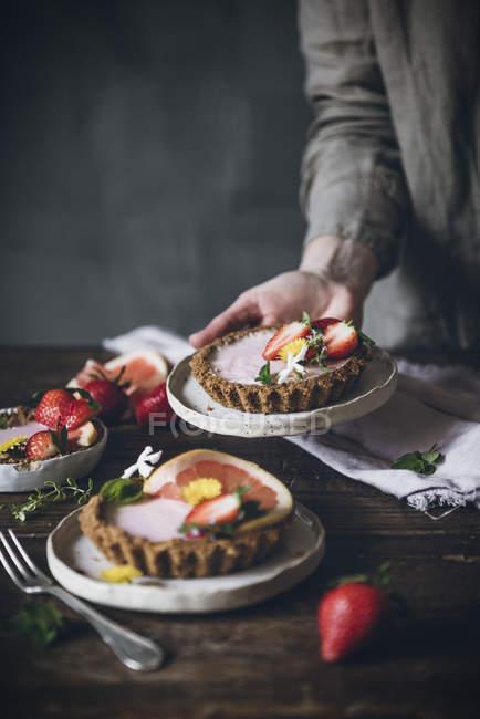 Persona irriconoscibile che serve piatti di torte di agrumi guarnite con fragole su tavola di legno — Foto stock