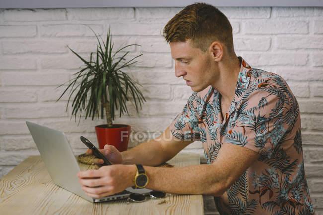 Uomo concentrato utilizzando smartphone mentre si utilizza il computer portatile a tavola in caffetteria — Foto stock