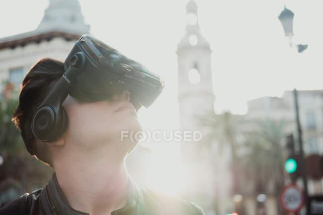 Hombre inteligente usando gafas VR mirando a su alrededor en la calle de la ciudad con luz solar vibrante de nuevo iluminado - foto de stock