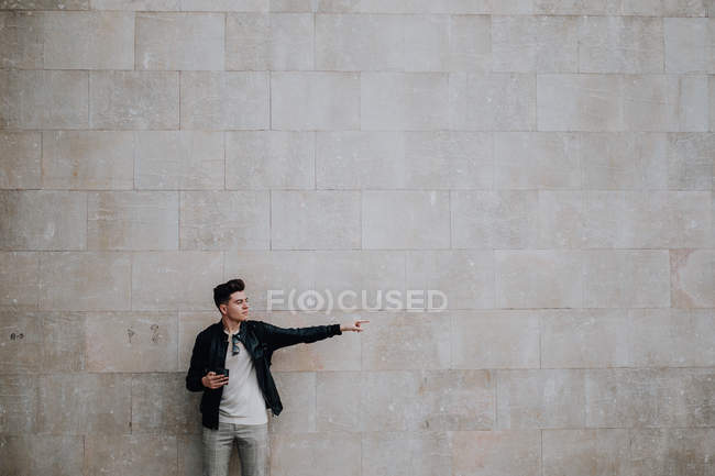 Smart stylish man holding mobile phone and pointing away against plain brick wall — Stock Photo