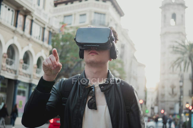 Smart man using VR goggles looking around on city street in vibrant sunlight back lit — Stock Photo