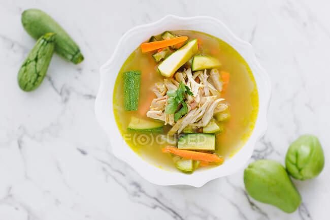 Подается миска куриного супа с морковью и цуккини на столе с цуккини и разделочной доской — стоковое фото