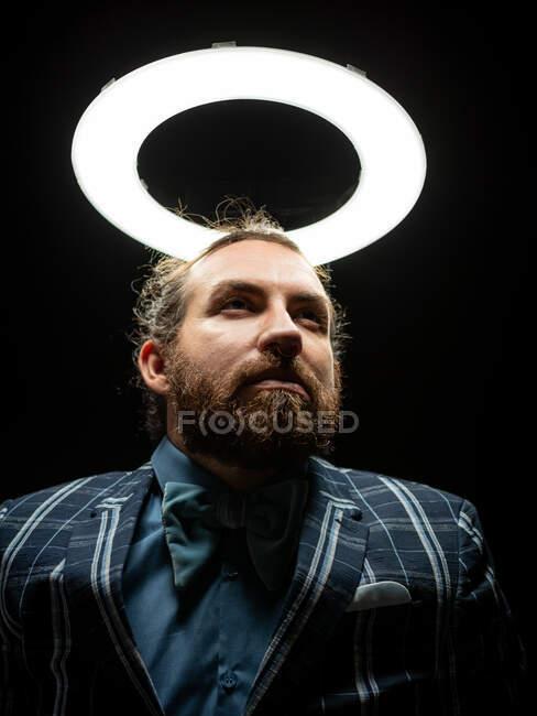 Умный бородатый человек под круговым светом на черном фоне — стоковое фото