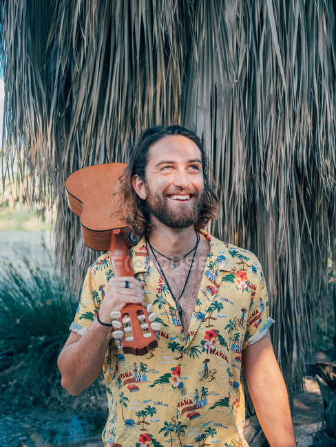 Pensive bearded hipster man traveling in jungle with ukulele — Stock Photo