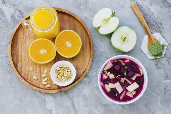 De arriba servido las naranjas, los cacahuetes y el jugo de naranja sobre la mesa con las manzanas, los condimentos y el plato de la remolacha - foto de stock