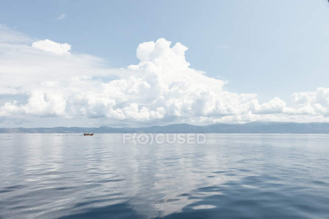 Picturesque view of cloudy sky and blue reflecting water with remote boat in sunshine, Halkidiki, Greece — стокове фото
