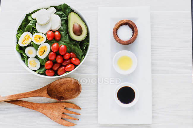 Подается миска салата со шпинатом, яйцами, авокадо, помидорами и сыром моцарелла на столе с приправами и соусами — стоковое фото