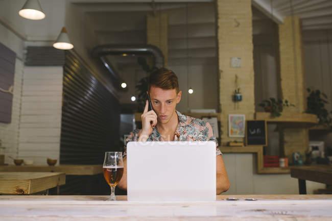 Uomo concentrato che parla sullo smartphone mentre utilizza il computer portatile a tavola con bevanda — Foto stock