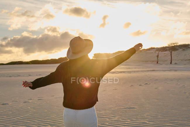 Vista posteriore della donna viaggiatrice in cappello in piedi nel deserto sabbioso remoto al tramonto a Tarifa, Spagna — Foto stock