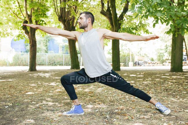 Красивый сфокусированный мускулистый мужчина в спортивной одежде, вытягивающий руки и ноги в парке в солнечный день — стоковое фото