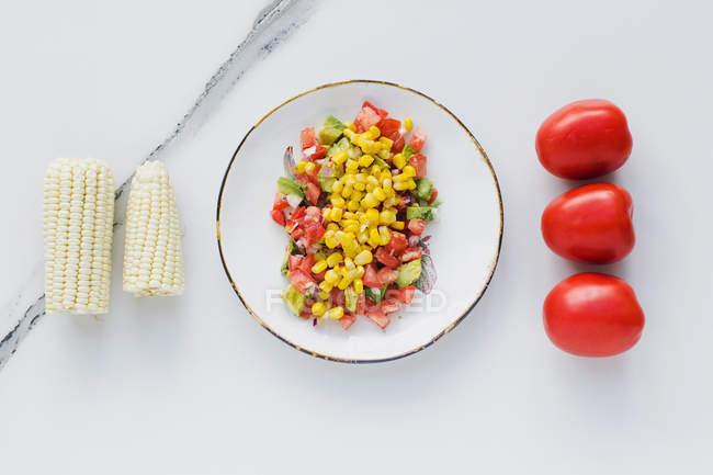 Tigela servida com milho e tomates cortados, abobrinha na mesa — Fotografia de Stock