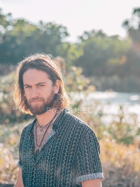 Молодой сварливый бородатый хипстер возле реки смотрит в камеру солнечным летом — стоковое фото