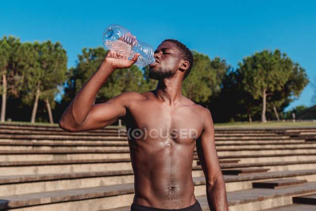 Fuerte atlético hombre afroamericano beber agua de la botella de plástico en el día caliente brillante - foto de stock