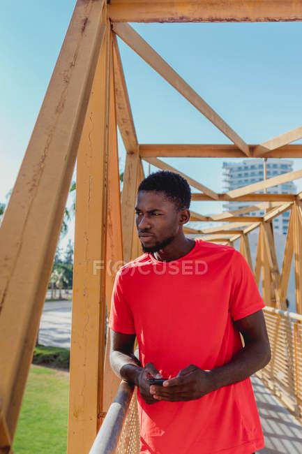 Sporty black man in red t-shirt walking on big iron bridge in bright daytime looking away — Stock Photo