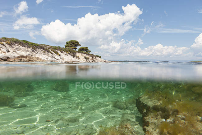 Picturesque view of rocky island and sea bottom on sunny summer day in Halkidiki, Greece — Stock Photo