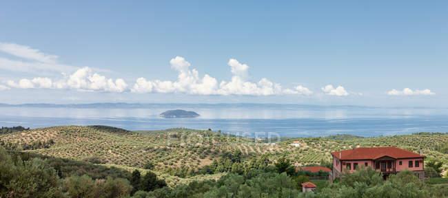 Vue panoramique du bord de mer vert avec la villa rouge et la plantation verte sur le rivage contre la mer de cristal dans la lumière du soleil, Grèce — Photo de stock