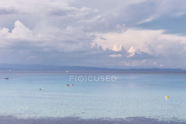 Peaceful sea water with people swimming in calm weather under cloudy sky, Halkidiki, Greece — стокове фото