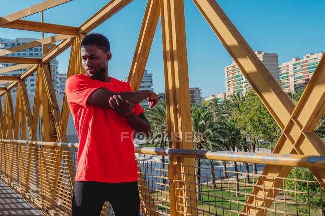 Homme noir sportif s'étirant et se réchauffant sur un pont de fer pendant la journée ensoleillée — Photo de stock