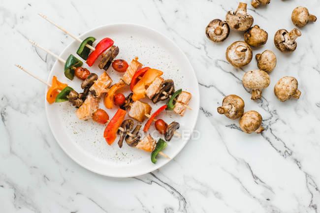 Trozos de tomates cherry, pimientos dulces, salmón y champiñones servidos en pinchos sobre la mesa con champiñones - foto de stock