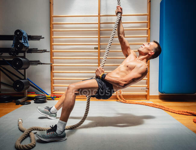 Side view of shirtless muscular sportsman climbing up rope while exercising in modern gym — Stock Photo