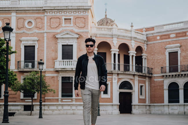 Handsome stylish guy with modern hairstyle wearing sunglasses outside. — Stock Photo