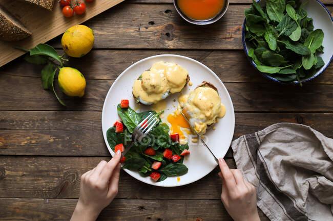 Pessoa comendo ovos mexidos em pão com molho verde e tomate — Fotografia de Stock