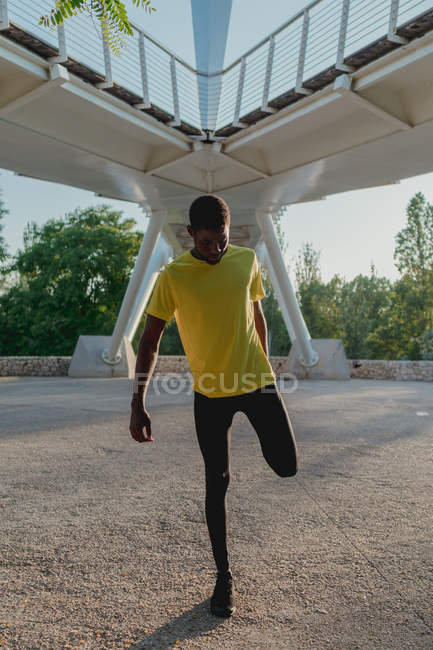 From below sporty African American jogger stretching legs before training under bridge in bright sunny daytime — Stock Photo