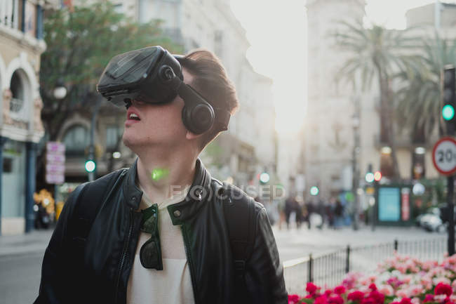 Умный человек в защитных очках осматривает городскую улицу в ярком солнечном свете — стоковое фото