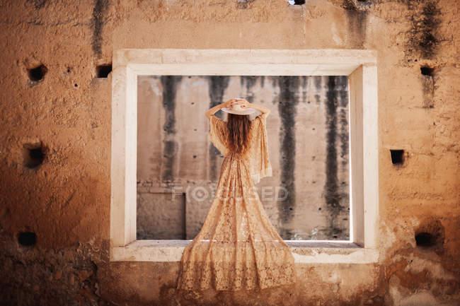 У бежевому мереживному одязі, на стіні покинутого будинку і капелюсі. — стокове фото