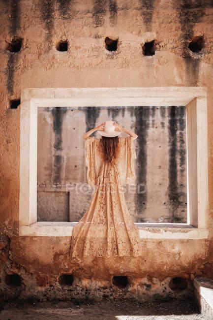 Елегантна жінка в довгому одязі на вікні. — стокове фото