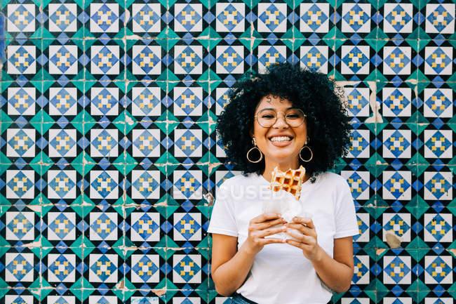 Giovane donna in t-shirt bianca in piedi da parete piastrelle colorate, mangiare waffle e sorridere alla macchina fotografica — Foto stock