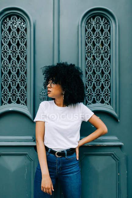 Mulher muito étnica em t-shirt branca e jeans encostados na porta verde e olhos fechados — Fotografia de Stock